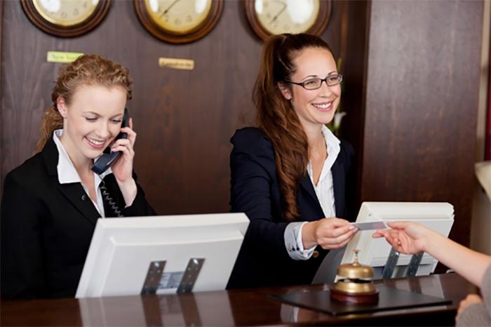 Lễ tân khách sạn thực hiện check in cho khách